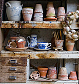 Plant pots, vintage crockery and Easter wreath in old cabinet