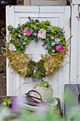 Summer wreath of roses, lady's mantle and straw