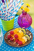 Fruit skewers in rainbow colors and paper straws for a party