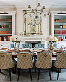 Upholstered chairs with rings on backs around elegantly set table in dining room