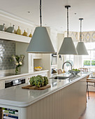 Pale blue lamps above island counter in classic kitchen-dining room