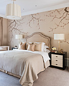 Elegant bedroom in nude shades with Japanese-style branches painted on wall
