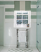 Heated towel rail below window in bathroom with mint-green stripes
