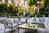 Masonry bench on elegant terrace in courtyard garden