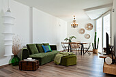 Alte Holztruhe als Beistelltisch und grüne Polstermöbel in offenem Wohnraum