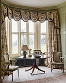 Table and Baroque chairs in bay window with opulent curtains