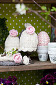 Knitted egg cosies with crocheted flowers