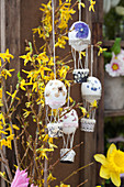 Hot-air balloons made from Easter eggs hung from forsythia branches