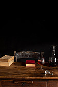 Wooden table with glass of cognac, decanter and old books