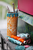 Tin can covered with wrapping paper and crocheted trim used to hold crochet hooks
