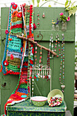 Colourful crocheted scarf and necklaces hung on green wooden door