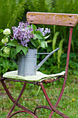 Bouquet of lilac and viburnum in zinc watering can on chair in garden