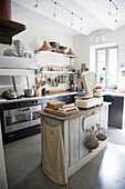 Modern black kitchen with old kitchen island and nostalgic decorations