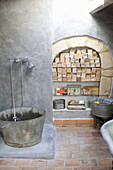 Shower with old metal tub and shelf in the arch with soap collection