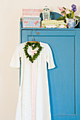 Nostalgic nightgown and heart-shaped wreath on blue cupboard