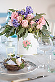 Bouquet with hyacinths, roses and eucalyptus on a laid table