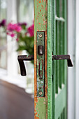 Battered green door with old door handles