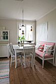 Chairs with turned spindles and upholstered bench around dining table on board floor