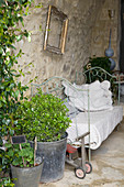 Old metal bed as sofa in the nostalgic courtyard with natural stone wall
