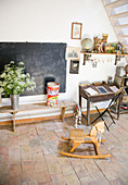 Rocking horse in front of old bench, blackboard and desk with junk as decoration