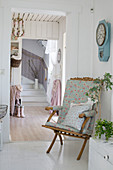 Folding chair with floral upholstery in shabby-chic hallway