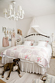 Dog at foot of bed with valance in romantic, white bedroom