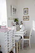 Chest of drawers next to sewing table in shabby-chic style