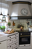 Clock on mantel hood in vintage-style kitchen