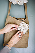Women's hands arrange a flower brooch on a cloth bag
