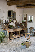 Old workbench as planting table with objects and decorative utensils in a courtyard