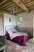 Metal bed in a rustic bedroom with terracotta tile floor