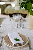 Leaf on cloth napkin with a monogram on a set table
