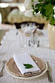 Blatt auf Stoffserviette mit Monogramm auf gedecktem Tisch