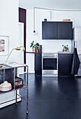 Kitchen with black cupboard fronts and black linoleum floor