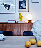 View over dining table to teak sideboard with sculpture and lamp, above artwork