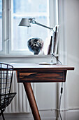 Desk with lamp in front of window
