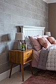 Retro bedside cabinet in feminine bedroom in pastel shades