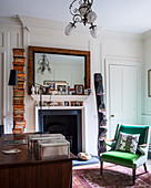 Green armchair in classic study with open fireplace
