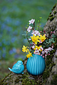 Spring bouquet of daffodils, blood plum, and boxwood in a turquoise vase next to a ceramic bluebird decoration