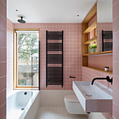 Bathtub below window in bathroom with pink wall tiles