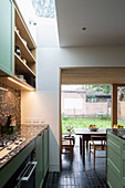 Kitchen with black terrazzo elements, skylight and dining area in extension