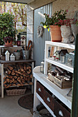 Firewood, gardening utensils and vintage-style decorations on shelves against outside wall