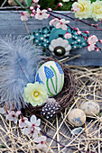 Easter basket with hand-painted Easter egg, feathers, primrose flower and branch of blood plum