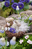 Easter basket with flowers, feathers and Easter bunny