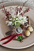 Posy of snowdrops, sprigs of purple-leaf plum tree blossom, feathers and ivy leaf decorating plate for Easter meal