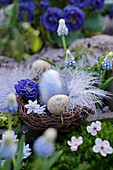 Easter basket with Easter eggs, flowers and feather