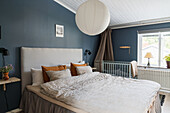 Double bed and baby cot in bedroom with blue walls