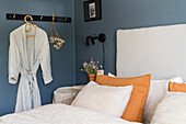 Double bed with high headboard in bedroom with blue walls
