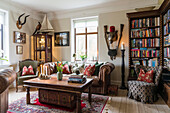 Antique bookcase, leather couch and hunting trophies in the living room