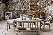 Garden furniture on the terrace in front of a rustic natural stone wall